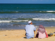 28 OCTOBER 2012 - SAI BURI, PATTANI, THAILAND:  A Muslim couple sit by themselves on Wasukrit beach in Sai Buri, Thailand. Sai Buri, in Narathiwat province, Thailand, has been the scene of several bloody attacks in Thailand's long running Muslin insurgency. In September, 2012, a large car bomb was detonated in front of a Buddhist owned business in the village killing six and injuring scores of people. In October, 2012, in a possible revenge attack, hand grenades were rolled into a crowd of Muslim diners, injuring 16. More than 5,000 people have been killed and over 9,000 hurt in more than 11,000 incidents, or about 3.5 a day, in Thailand's three southernmost provinces and four districts of Songkhla since the insurgent violence erupted in January 2004, according to Deep South Watch, an independent research organization that monitors violence in Thailand's deep south region that borders Malaysia.   PHOTO BY JACK KURTZ