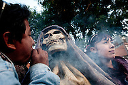 A man blows cigar smoke into the face of a large Sante Muerte statute to bless it while a girl poses for a photograph in Tipito Mexico City.