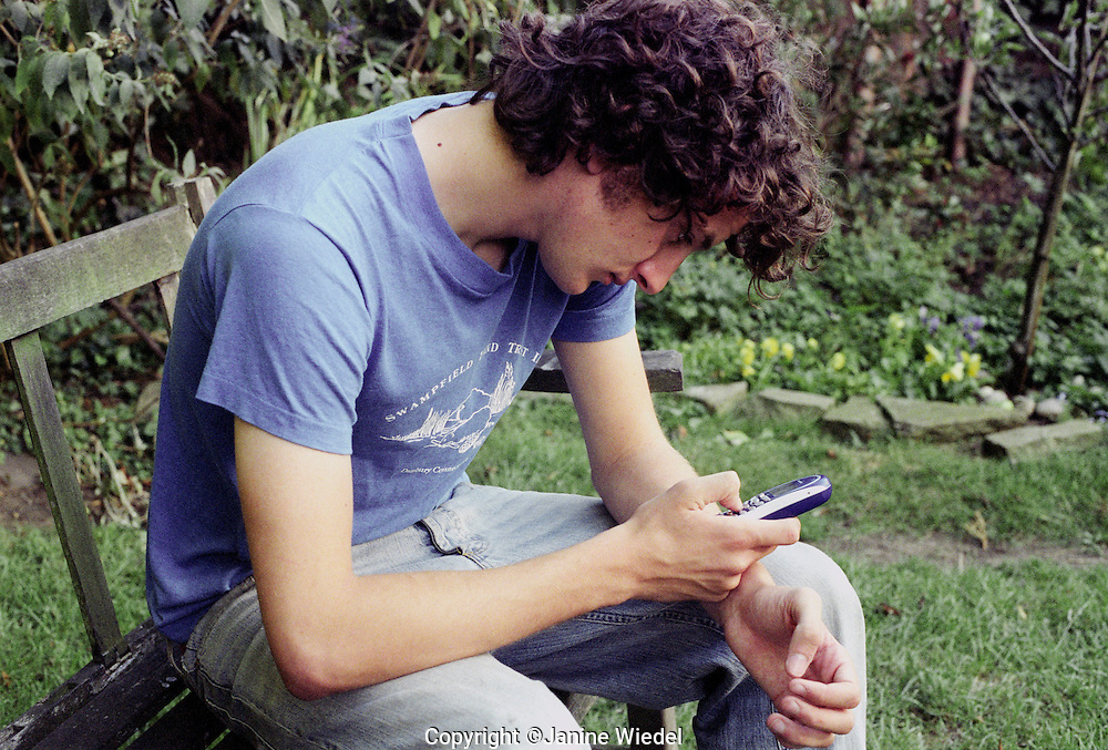 teenage boy sitting on bench  sending  text message to friend.
