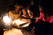 Abibatou Goudiaby, 21, sits with her children while they study at home in the light of an oil lamp in the village of Kagnarou, Senegal on Saturday May 29, 2010.