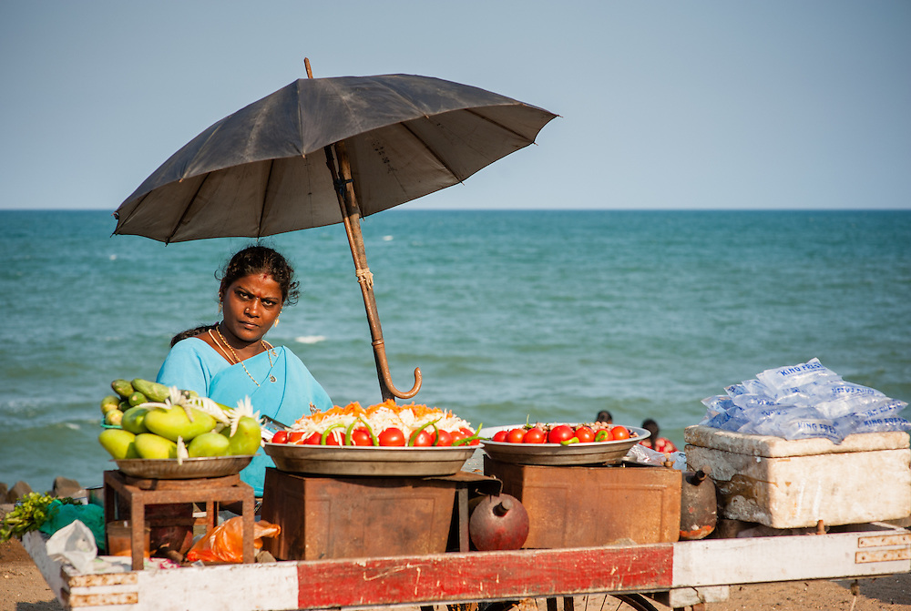 Woman under umbrella selling food at stall by the sea at Puducherry (India)