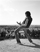 Young man standing on top of hill playing air guitar.