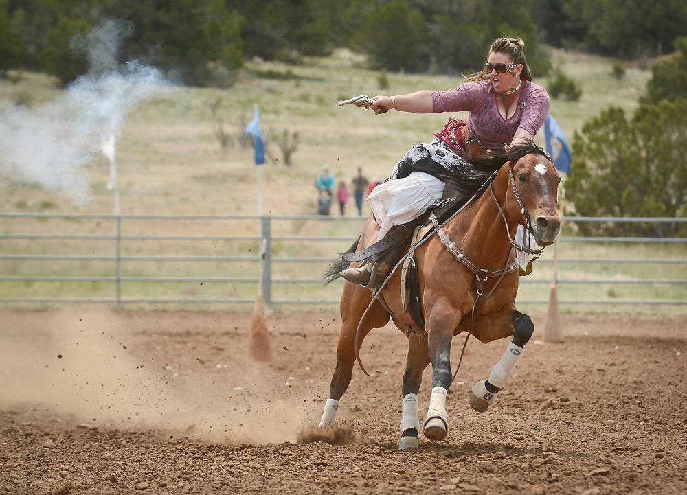 mkb062417h/metro/Marla Brose --  Willow Romero of Moriarty, riding  Dually, competes in a mounted shooting contest in End of Trail 2017, The World Championship of Cowboy Action Shooting, June 23, 2017, in Albuquerque, N.M. Horseback shooters fired at balloons mounted on cones as they raced around the arena. The embers from black powder popped the balloons. About 600 shooters, all dressed in Old West era attire, brought their pistols, rifles and shotguns to compete in the 36th annual shooting event at  Founders Ranch in Edgewood, N.M.  The public was welcome to watch on Friday and Saturday. The event ends on Sunday, a day which is closed to the public. (Marla Brose/Albuquerque Journal)