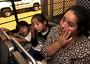 Elizabeth Nava Ausin, 32, right, and her daughters, Yokebed, 5, (left), and Samantha Rached, 10, slept in the sand in the desert for seven nights before crossing into the U.S. illegally from Mexico near Lukeville, Arizona.  Their journey to Phoenix ended when a Border Patrol agent noticed the weighted bed of the pickup truck in which 18 illegal immigrants rode and stopped the vehicle.  They wait on a bus in Sells to be deported.