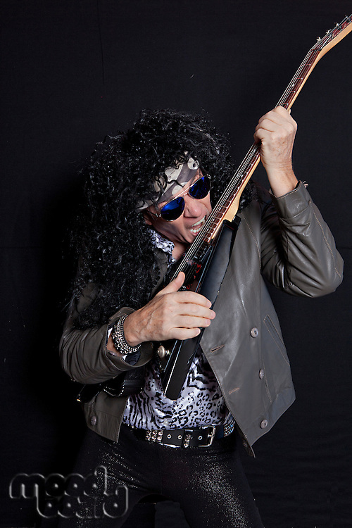 Senior man biting his guitar while performing over black background