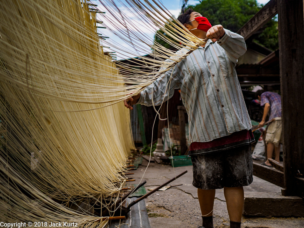 "29 DECEMBER 2018 - BANGKOK, THAILAND: A woman checks for rain clouds while she stretches longevity noodles during the drying process in front of her family shophouse. The noodles can't be left out if it rains. The family has been making traditional ""mee sua"" noodles, also called ""longevity noodles"" for three generations in their home in central Bangkok. They use a recipe brought to Thailand from China. Longevity noodles are thought to contribute to a long and healthy life and  are served on special occasions, especially Chinese New Year, which is February 4, 2019. These noodles were being made for Chinese New Year.      PHOTO BY JACK KURTZ"