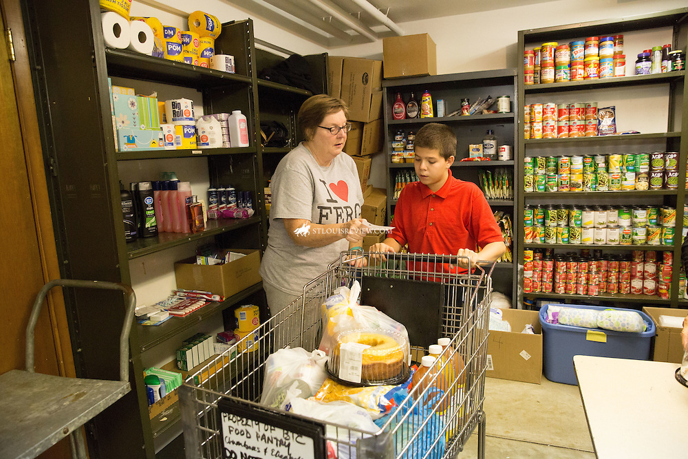 Lisa Johnston | lisajohnston@archstl.org | Twitter: @aeternusphoto The Society of St. Vincent de Paul operated the Blessed Teresa of Calcutta Parish food pantry operates once a month to help the poor supplement their needs. Volunteer Kathy Noelker loaded food into a cart pushed by Blessed Teresa of Calcutta seventh grader, Devon Tallen,who was helping from the school.