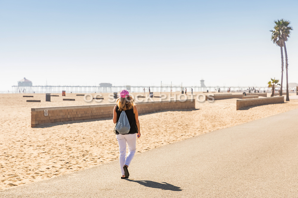 Girl Walking On The Huntington Beach Boardwalk With Pier In Background