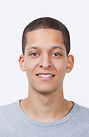 Portrait of young mixed race man smiling against white background