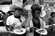 Two people eating jerk chicken and rice, at a food stall, Notting Hill Carnival, London, UK, 1983.