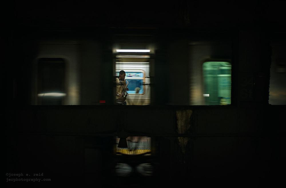 Man playing saxophone on subway platform as trains pass