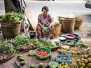 16 JUNE 2013 - YANGON, MYANMAR:  A woman sells vegetables on a street in Yangon. Yangon, formerly Rangoon, is the largest city in Myanmar. It is the former capital of the Southeast Asian country. It's still Myanmar's economic capital.      PHOTO BY JACK KURTZ