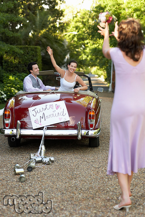 Bride and groom in vintage car bride throwing bouquet to woman