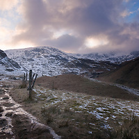 Footpath leading into mountains on a winter evening