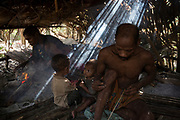 Champ prepares darts next to his two young children inside their hut.<br /> <br /> Evidence suggests that the Maniq, a Negrito tribe of hunters and gatherers, have inhabited the Malay Peninsula for around 25,000 years. Today a population of approximately 350 maniq remain, marooned on a forest covered mountain range in Southern Thailand. Whilst some have left their traditional life forming small villages, the majority still live the way they have for millennia, moving around the forest following food sources. <br /> <br /> Quiet and reclusive they are little known even in Thailand itself but due to rapid deforestation they are finding it harder to survive on the forest alone and are slowly being forced to move to its peripheries closer to Thai communities.