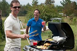 Two men enjoying a barbecue in the backyard