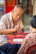 "22 JANUARY 2013 - BANGKOK, THAILAND:  A calligrapher works on Chinese New Year for customers at his table on Charoen Krung Road in Bangkok's Chinatown district. Chinese New Year is not an official public holiday in Thailand, but it is one the biggest celebrations in the Bangkok, which has a large Chinese population. Chinese New Year is February 10 this year. It will be the ""Year of the Snake.""     PHOTO BY JACK KURTZ"