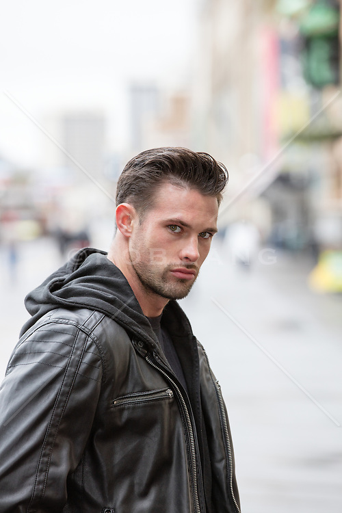 sexy man in a leather jacket outdoors