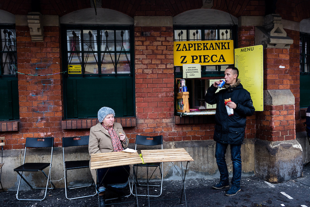 People eating from a curbside lunch counter in the city of Warsaw, Poland