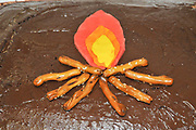 Campfire with flame and pretzel logs decorate a chocolate birthday cake for a firefighter expert