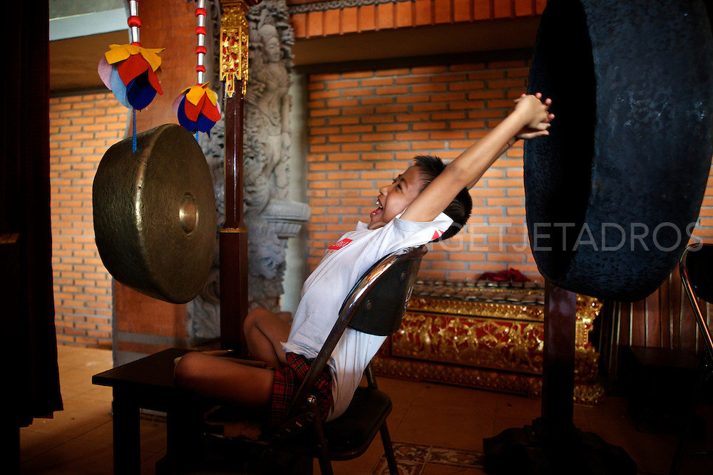 A young Balinese boy yawning during a music practise in a temple.<br />
