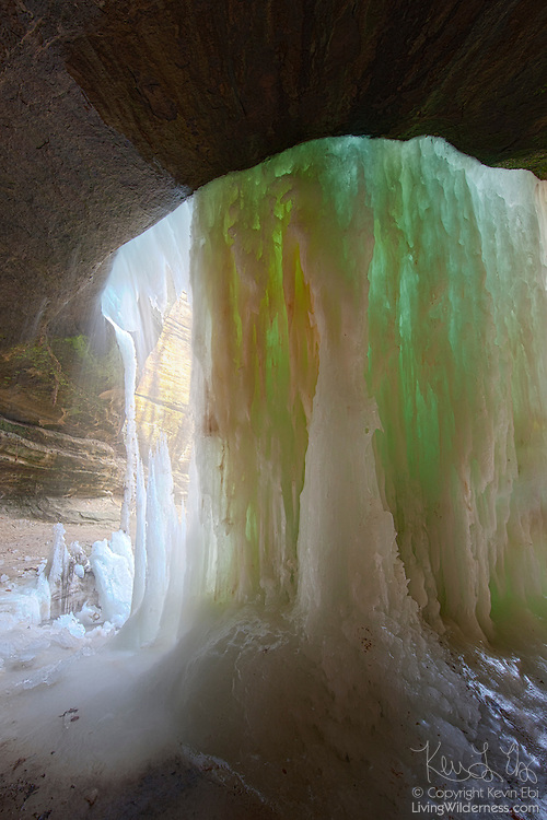 LaSalle Canyon Falls, viewed from behind, begins to thaw in late winter in Starved Rock State Park near LaSalle, Illinois. The 20-foot (6-meter) waterfall can completely freeze in winter. As it thaws, the ice thins and can become almost translucent, forming dramatic green and blue colors as the ice of varying thickness refracts sunlight to different degrees. Here, part of the icefall has melted as is once again flowing as a waterfall.