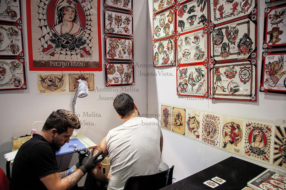 Tattoo artist performs his art to his client during the 'Tattoo Expo', at Palermo. Tattoo artists from all over the world met at the I° Palermo Tattoo Expo, featuring many artists starting what would elaborate works of art to the customers.