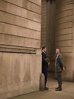 Two businessmen talking at entrance of monumental building