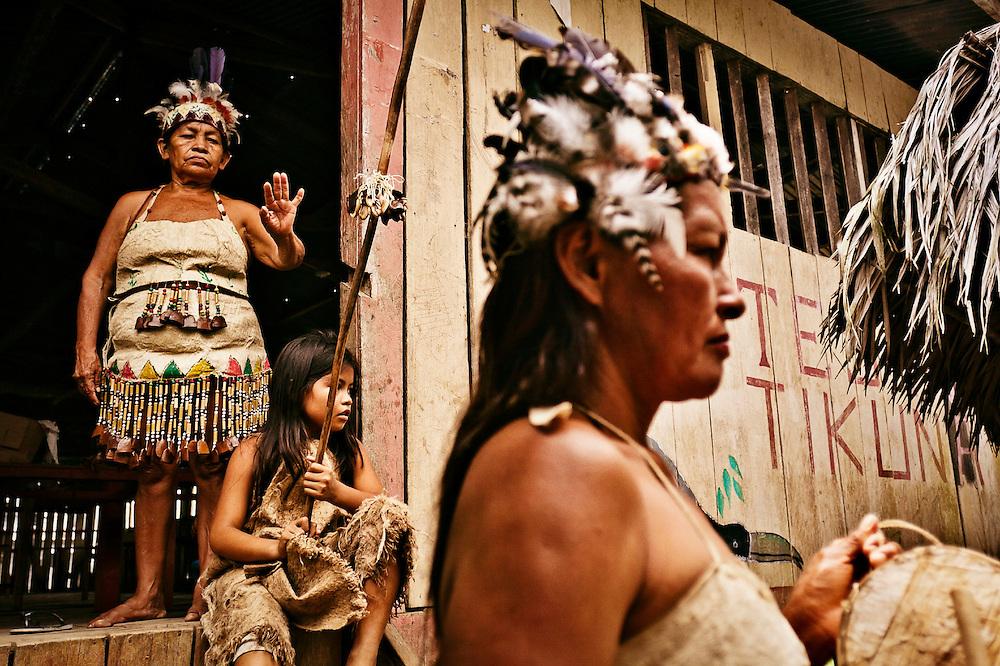 Colombia, Macedonia, 2010. Baile de disfraces. <br /> Los trajes tradicionales son hoy el atuendo de trabajo de las comunidades tikunas. Este grupo de mujeres espera la llegada de los turistas para vender la demostraci&oacute;n de unos de sus bailes t&iacute;picos alrededor de la fertilidad. Las mayores, aprendieron los cantos y movimientos como herencia de una cultura milenaria; las ni&ntilde;as lo reciben como mecanismo de inserci&oacute;n en la actividad econ&oacute;mica de la regi&oacute;n donde hoy prima el turismo. En las tareas del hogar, los nativos incluyen la fabricaci&oacute;n de artesan&iacute;as como medio de sustento.<br /> <br /> Dance of disguises. <br /> Traditional costumes are today the work attire of the Tikunas.  This group of women await the arrival of tourists, to sell tickets for their performance of one of their typical dances about the fertility. The eldest learned the songs and movements as part of their inheritance from a millennium of culture; girls now are taught it as a way to be included in the economic activity of the region where today tourism prevails.  Household tasks now include the manufacture of handicrafts for sale as a means of livelihood.