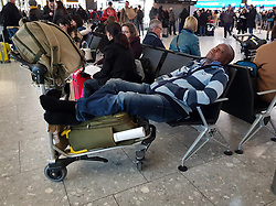 © Licensed to London News Pictures. 11/12/2017. London, UK. A passenger sleeps on a seat at Heathrow's Terminal 5 after yesterday's snow continues to affect transport. British Airways had already cancelled 30 flights before 10am today. Photo credit: Peter Macdiarmid/LNP