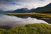 A pond reflecting the mountains and farm Brettingsstaðir in Flateyjardalur, North Iceland. Brettingsstaðir og fjöllin spelast í tjörn í Flateyjardal.