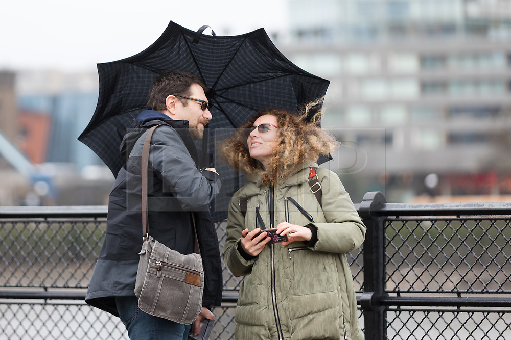 © Licensed to London News Pictures. 08/02/2019. London, UK.  A couple shelter under an umbrella during wet and windy weather near Tower Bridge. Storm Erik is the first named storm of 2019 with gale force winds and wet weather affecting most of the UK today. Photo credit: Vickie Flores/LNP