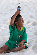 At the Chao Leh (Sea Gypsy) village. Kids playing at the beach. Boy with Coke bottle.