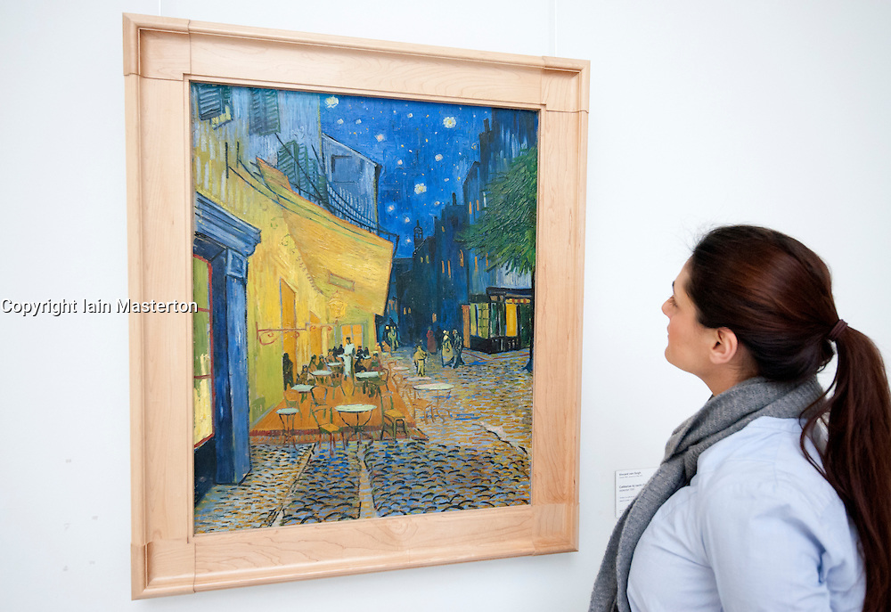 Woman looking at painting Terrace of a Cafe at Night (place du Forum) by Vincent van Gogh at Kroller-Muller Museum in The Netherlands