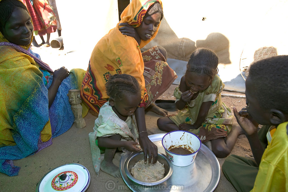 (MODEL RELEASED IMAGE). Squatting near the fire with her children, Sudanese Refugee D'jimia Ishakh Souleymane serves out aiysh, the thick porridge that this refugee family eats three times a day. Despite losing almost everything in their flight from militia attacks, D'jimia keeps her improvised household as orderly as possible. To cover the ground inside, the family hauled in clean sand from the dry riverbed. D'jimia and the children sleep on two blankets, which she constantly airs out and washes. (Supporting image from the project Hungry Planet: What the World Eats.)
