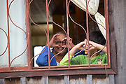 A grandmother and grandson making heart shapes with their hands out of the window smiling.
