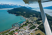 """Aerial view of Haines, Alaska, USA. Flightseeing from Skagway or Haines is a spectacular way to see Glacier Bay National Park, in Southeast Alaska. We were bedazzled by Mountain Flying Service's 1.3-hour West Arm tour from Skagway. Glacier Bay is honored by UNESCO as part of a huge Biosphere Reserve and World Heritage site shared between Canada and the United States. In 1750-80, Glacier Bay was totally covered by ice, which has since radically melted away. In 1794, Captain George Vancover found Icy Strait on the Gulf of Alaska choked with ice, and all but a 3-mile indentation of Glacier Bay was filled by a huge tongue of the Grand Pacific Glacier, 4000 feet deep and 20 miles wide. By 1879, naturalist John Muir reported that the ice had retreated 48 miles up the bay. In 1890, """"Glacier Bay"""" was named by Captain Beardslee of the U.S. Navy. Over the last 200 years, melting glaciers have exposed 65 miles of ocean. As of 2019, glaciers cover only 27% of the Park area. Since the mid 1900s, Alaska has warmed 3 degrees Fahrenheit and its winters have warmed nearly 6 degrees. Human-caused climate change induced by emissions of greenhouse gases continues to accelerate warming at an unprecedented rate. Climate change is having disproportionate effects in the Arctic, which is heating up twice as fast as the rest of Earth."""