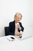 Smiling senior businesswoman having coffee while using laptop at desk in office