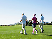 Three young golfers on course back view