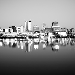 Peoria Illinois skyline at night black and white photo with downtown city buildings reflection on the Illinois River and the Spirit of Peoria paddlewheel riverboat.