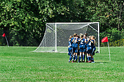 Youth girls soccer team huddles before match.