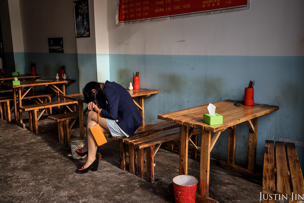 A woman from the country side falls asleep during work in a restaurant in the heart of a relocation housing estate in China's southwestern Chongqing city. <br /> <br /> She, like her clients, were recently relocated from nearby villages that were razed by the government to make way for urban high-rises. <br /> <br /> China is pushing ahead with a dramatic, history-making plan to move 100 million rural residents into towns and cities between 2014 and 2020 &mdash; but without a clear idea of how to pay for the gargantuan undertaking or whether the farmers involved want to move.<br /> <br /> Moving farmers to urban areas is touted as a way of changing China&rsquo;s economic structure, with growth based on domestic demand for products instead of exporting them. In theory, new urbanites mean vast new opportunities for construction firms, public transportation, utilities and appliance makers, and a break from the cycle of farmers consuming only what they produce.<br /> <br /> Urbanization has already proven to be one of the most wrenching changes in China&rsquo;s 35 years of economic reforms. Land disputes rising from urbanization account for tens of thousands of protests each year.