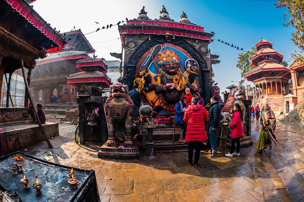 Hindu worshippers make offerings to the statue of Kali, Shiva's 6-armed destructive form, Durbar Square, Kathmandu, Nepal.