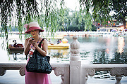 A Chinese girl watches her smartphone on the Bei Hai lake in Beijing, China, July 20, 2014.<br /> <br /> Smartphones are an essential tool of Chinese ordinary life. Everywhere in China, people use them to take pictures to share online, to talk and chat, to play videogames, to get access to the mainstream information, to get connected one each other. In the country where the main global social media are forbidden - Facebook, Twitter and Youtube are not available  -, local social networks such as WeChat have a wide spread all over the citizens. The effect is an ordinary and apparently compulsive way to get easy access to digital technology and modern way of communication. <br /> A life through the display. Yes, We Chat.<br /> <br /> © Giorgio Perottino