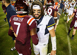 Sep 3, 2017; Landover, MD, USA; West Virginia Mountaineers quarterback Will Grier (7) talks with  at FedEx Field. Mandatory Credit: Ben Queen-USA TODAY Sports