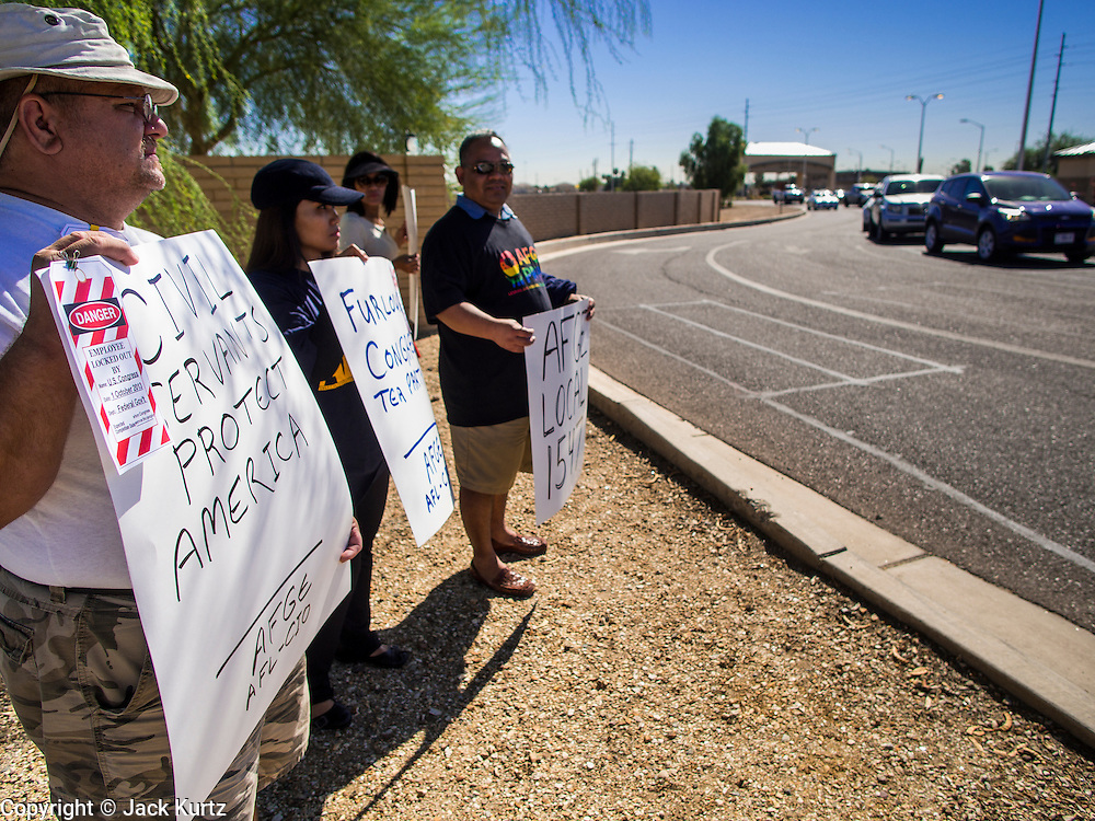 02 OCTOBER 2013 - GLENDALE, AZ: Furloughed federal employees, workers at Luke Air Force Base, picket the base Wednesday. The furloughed workers, all civilian employees and members of AFGE at Luke Air Force Base, protested the partial shutdown of the US government. The American Federation of Government Employees (AFGE) is the largest federal employee union representing 650,000 federal and D.C. government workers. Similar protests were held across the country as the partial government shutdown entered its second day.       PHOTO BY JACK KURTZ