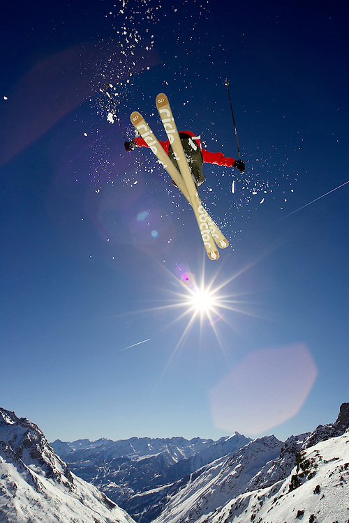 Male Skier jumps from rock on mountainside. Serre Chevalier, France