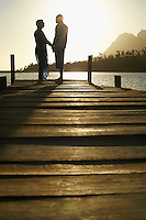 Couple standing on dock by lake holding hands side view.