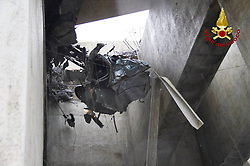 August 14, 2018 - Genoa, Italy - A mangled car hangs from wires after a highway bridge has partially collapsed, prompting fears of injuries and deaths. (Credit Image: © Fotogramma/Ropi via ZUMA Press)
