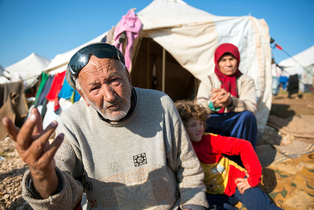 Muhammed Ramadan, age 90, sitting with family outside his tent at the displaced persons camp in Atmeh, Syria. They are from Idlib Province.
